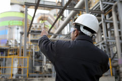 Engineer oil refinery. Oil refinery engineer pointing against pipeline Stock Images