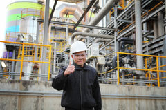 Engineer oil refinery. Industrial engineer with thumbs up standing beside pipeline inside oil refinery Royalty Free Stock Image