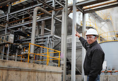 Engineer oil refinery. Engineer pointing against pipeline inside oil refinery Stock Images