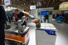 Engineer operates industrial KUKA robot in booth of Huawei company Stock Photos