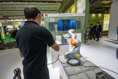 Engineer operates industrial KUKA robot in booth of Huawei company Royalty Free Stock Photography