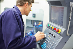 Engineer Operating Computer Controlled Milling Machine. Looking At Screen Stock Photo