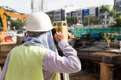 Engineer operating the dumpy automatic level instrument at const Stock Photo