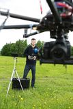 Engineer Operating UAV Octocopter in Park. UAV octocopter flying while male engineer operating it in background at park Royalty Free Stock Images