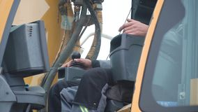 Engineer operator crane in action. Clip. Man in cabin controls the crane. He sit a top in crane cabin and working.  stock images