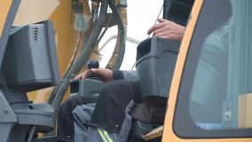 Engineer operator crane in action. Clip. Man in cabin controls the crane. He sit a top in crane cabin and working.  stock photo