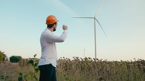 An engineer in an orange protective helmet and goggles looks at an electric power wind generator in a green field. After stock video