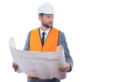 Engineer in orange vest reading drawing plan. Royalty Free Stock Photo