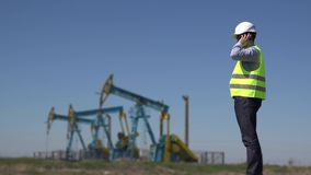 Engineer on phone near oil pumps reporting the available crude petroleum extraction installations supply working planning