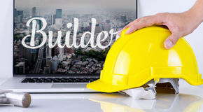 Engineer is picking up safety helmet with builder concept. On computer Stock Photos
