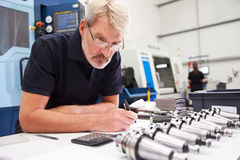 Engineer Planning Project With CNC Machinery In Background Royalty Free Stock Photo