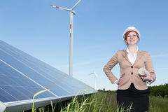 Engineer  posing with wind turbine and solar panels Royalty Free Stock Photos