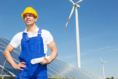 Engineer posing with wind turbine and solar panels Royalty Free Stock Image