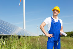 Engineer posing with wind turbine and solar panels Stock Image