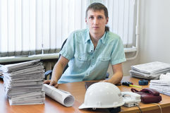 Engineer with project drawings in office. Engineer young adult male with project drawings in office. Working place. One man stock images