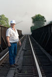 Engineer on Railroad. Railroad engineer walking track to check out situation of a fire near the track Royalty Free Stock Photo