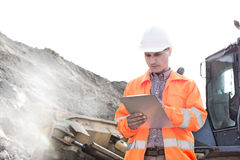Engineer reading clipboard at construction site Stock Photography