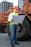 Engineer reading instruction to bulldozer at building site Stock Images
