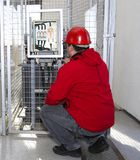 Electrician control high voltage fuse in power plant. Engineer in red control high voltage fuse in power plant stock image