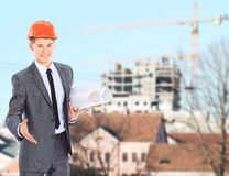 Engineer With Red Hard Hat. And Blueprint Under the Power Lines.Engineer holding blueprints at an electrical substation Stock Image