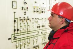 Engineer with red helmet control instruments in power plant royalty free stock photo