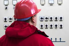 Engineer with red helmet reading instruments in power plant con. Technician with red helmet reading instruments in power plant control center royalty free stock images