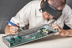 Engineer repairing circuit board. In computer equipment Royalty Free Stock Image