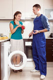 Engineer repairing a washing machine for  housewife in her home Royalty Free Stock Photo