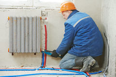 Engineer repairmen installing heating system Stock Photos