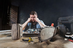 Engineer repairs laptop, repairman fix problem. With electronic components. Chainsaw and anvil on the table, engineering humor Royalty Free Stock Image