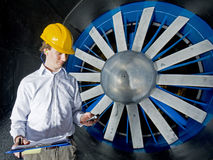Engineer, reporting in. A young engineer, reporting in after completing his inspection of a huge industrial windtunnel Stock Photography