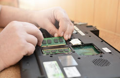 Engineer restores the laptop PC. Installing the hard drive hardware, RAM. Electronic repair shop, technology renovation. Engineer restores the laptop PC Stock Photo