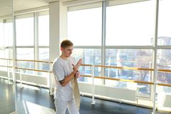 Engineer in sportswear rocking press in sport hall. Engineer rock press in sport hall, male want to perfect body. Barefoot tattooed man in white trousers lie on Royalty Free Stock Photo