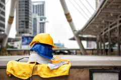 Engineer safety equipment at city for construction project. Many colorful Safety helmet hats, gloves, and yellow worker dress on concrete floor with blurred Royalty Free Stock Images