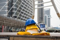 Engineer safety equipment at modern site. Safety helmet hats and yellow worker dress on footpath with blurred modern city  background. Engineering and Stock Photo