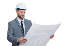 Engineer in safety hat  reading architecture plan. Stock Photos