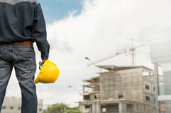 Engineer or safety officer holding yellow helmet with the building is background in construction site. royalty free stock photos