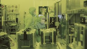 Two workers in the lab. Clean area. Nanotechnology. Sterile suit. Masked scientistе. Engineer scientist in sterile suits, mask. are in a clean zone looking at