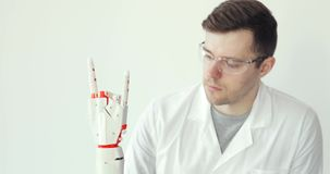 Engineer scientist is testing robotic prosthesis hand which makes movements with fingers. Attentively study how it`s