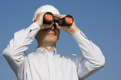 Engineer searching with binocular. Engineer with white hardhat looking through binocular Royalty Free Stock Images