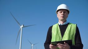 Engineer using digital tablet against wind turbine. Engineer with seriously face working with digital tablet against wind turbine on sunny day and looking at stock video