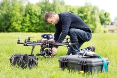 Engineer Setting Camera On UAV Helicopter. Young engineer setting SLR camera on UAV helicopter at park stock photos