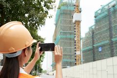 Engineer shooting a video on the phone. Rear view of female engineer in helmet shooting a video or making a photo of building on her mobile phone outdoors royalty free stock image