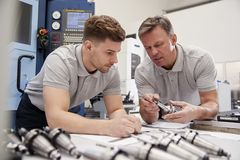 Free Engineer Showing Apprentice How To Measure CAD Drawings Stock Photo - 119420390