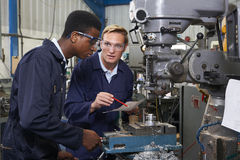 Engineer Showing Apprentice How to Use Drill In Factory. Experienced Engineer Showing Apprentice How to Use Drill In Factory Royalty Free Stock Photos