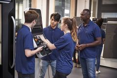 Engineer Showing Apprentices How To Use CNC Tool Making Machine royalty free stock image