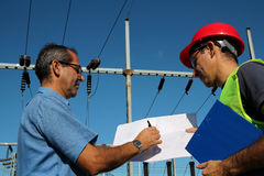 Engineer Showing Blueprint to Worker Stock Image