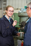 Engineer Showing Female Apprentice How To Use Drill. Engineer Shows Female Apprentice How To Use Drill stock photos
