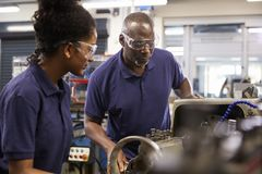 Engineer Showing Female Teenage Apprentice How To Use Lathe stock photos