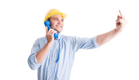 Engineer showing middle finger while talking on the phone Royalty Free Stock Photos